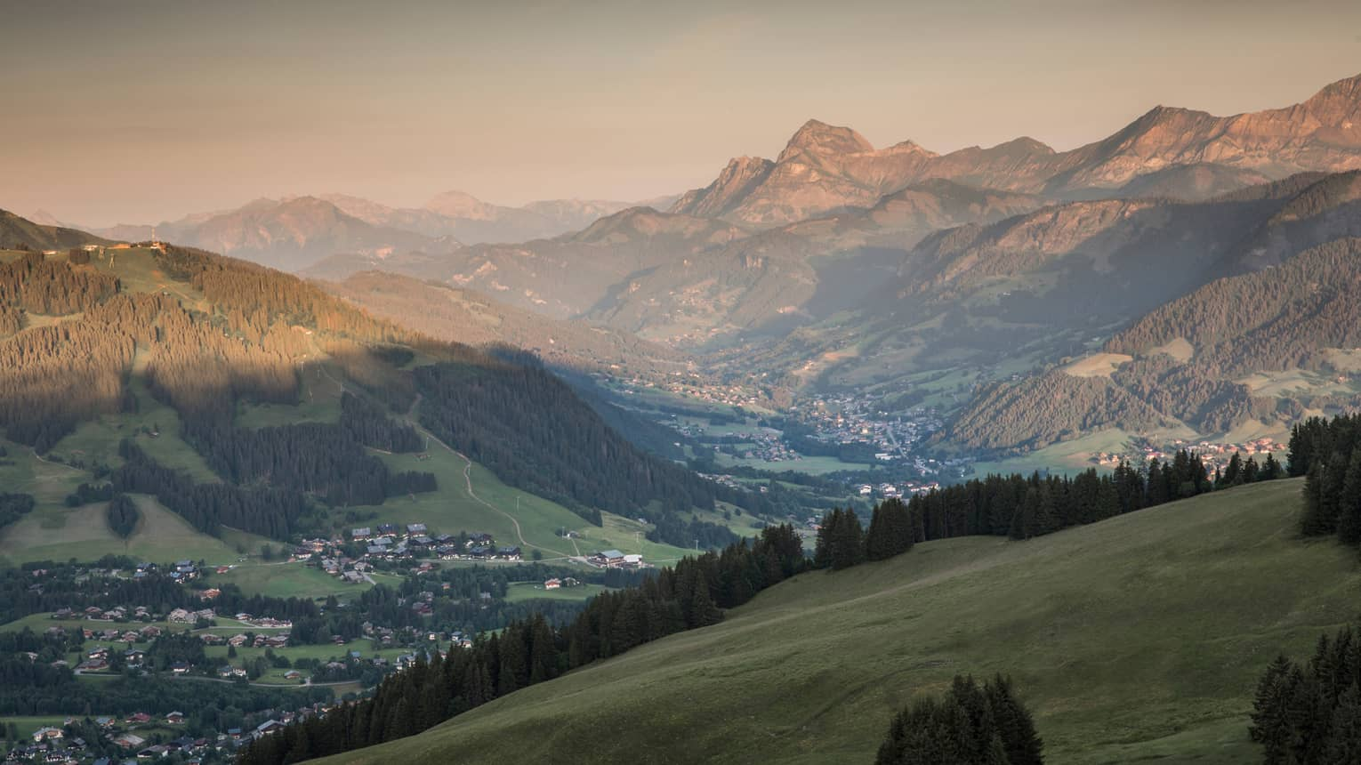 Sweeping views over green French Alps mountains at sunset