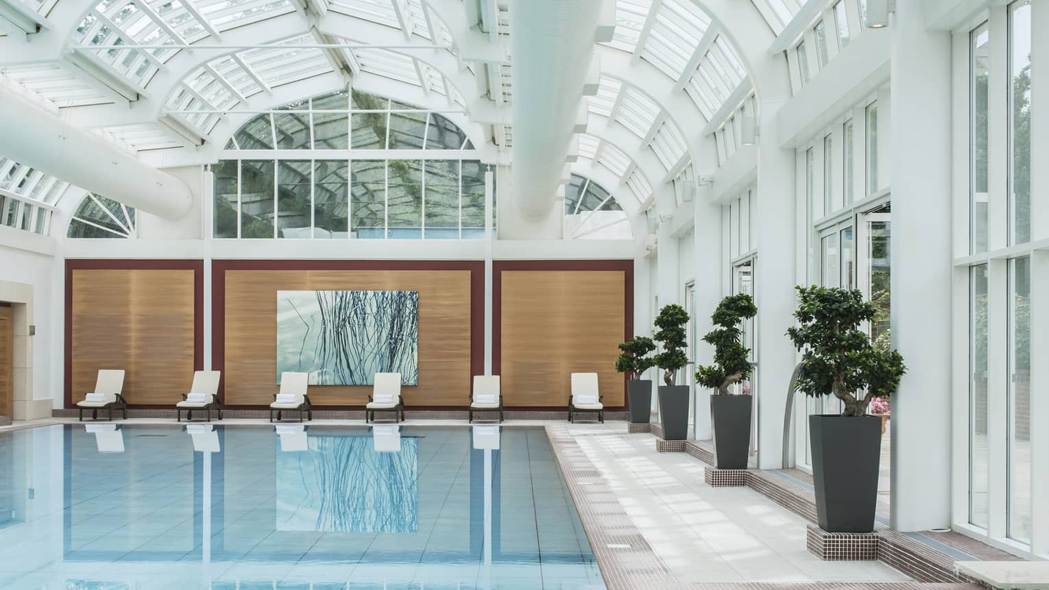 Lounge chairs, potted trees around indoor swimming pool under domed skylights, white beams