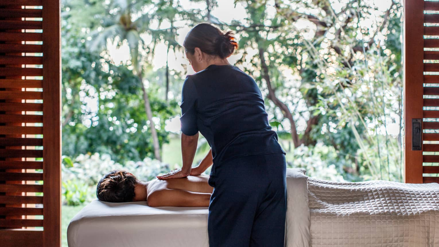 Spa staff massages woman's bare shoulders as she lies under sheet on massage table