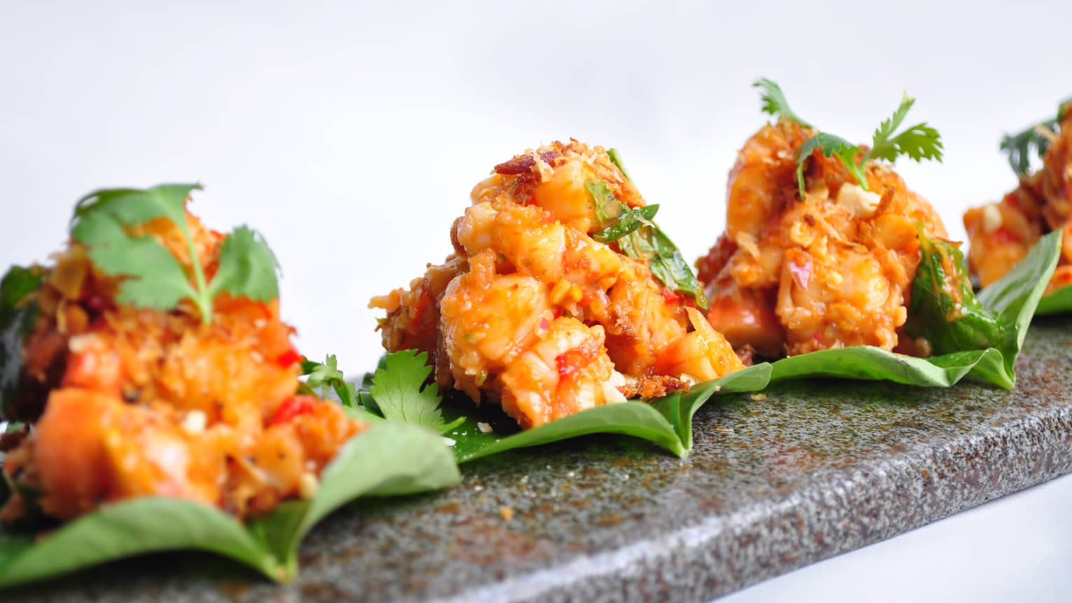Three Betel Leaves with prawn, coconut, baby ginger and miang sauce on grey serving platter
