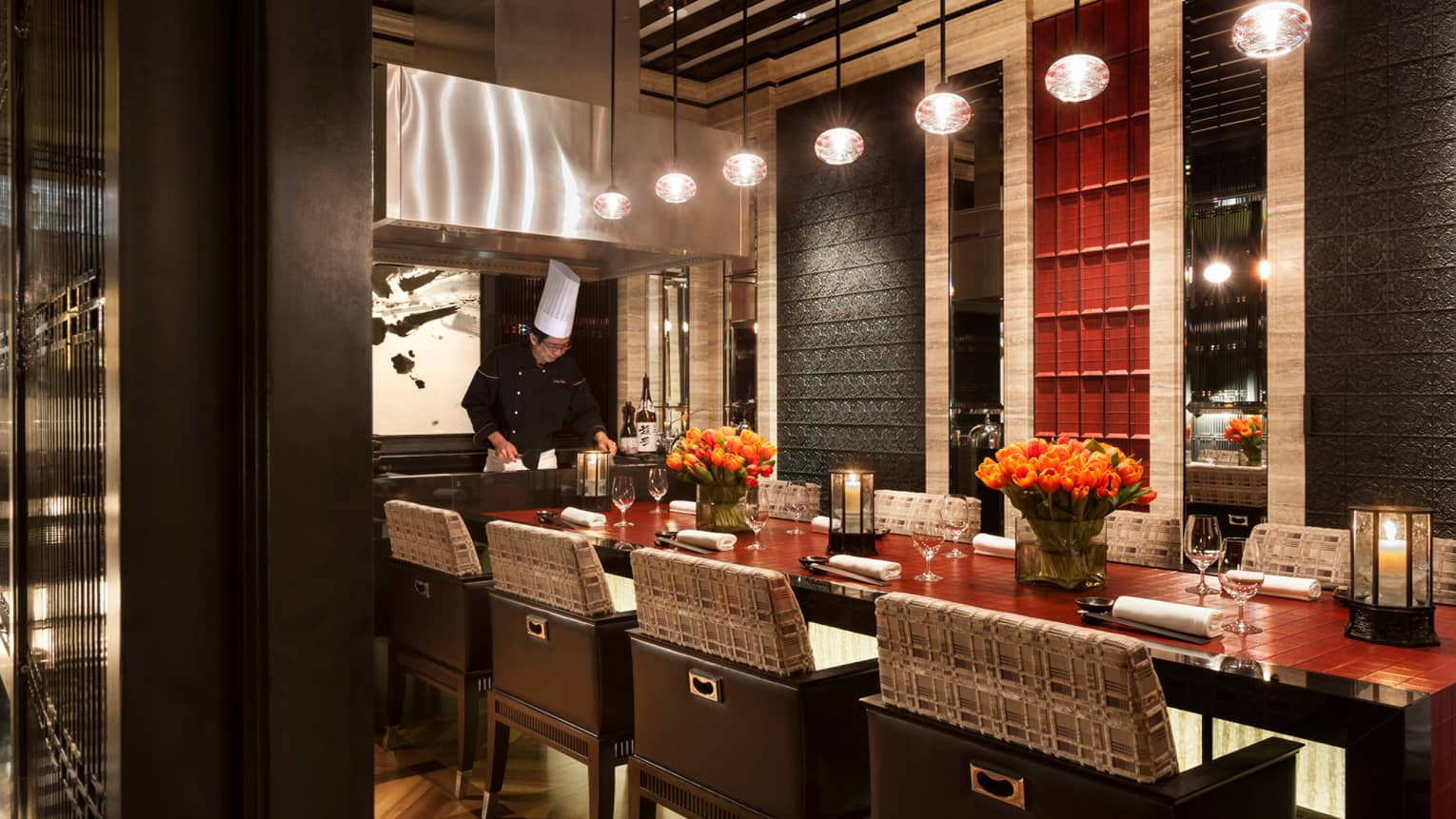 Chef works at head of Sintoho restaurant private dining table with candles in lanterns, orange tulips