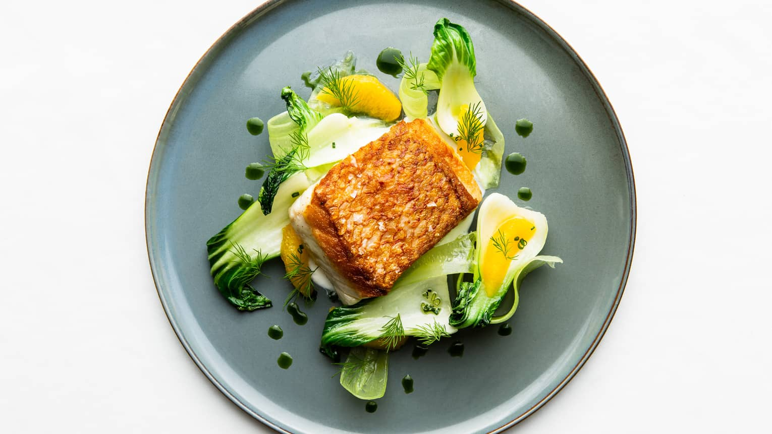 Aerial view of Florie's Seared Snapper Fillet on bed of bok choy and orange slices