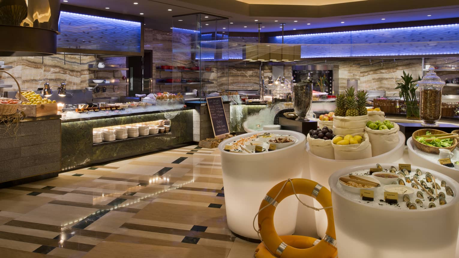 Bahrain Bay Kitchen buffet stations, large white bins of ice with seafood, fresh fruit, salad