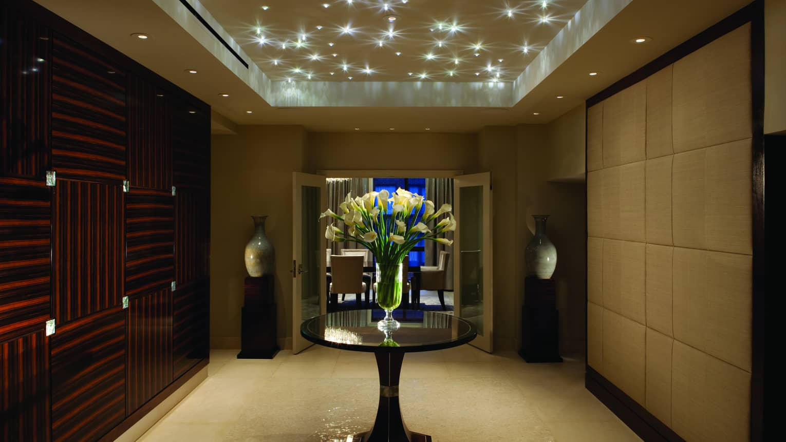 Royal Suite art deco-style private hallway under sparkling lights, door to private dining room at night