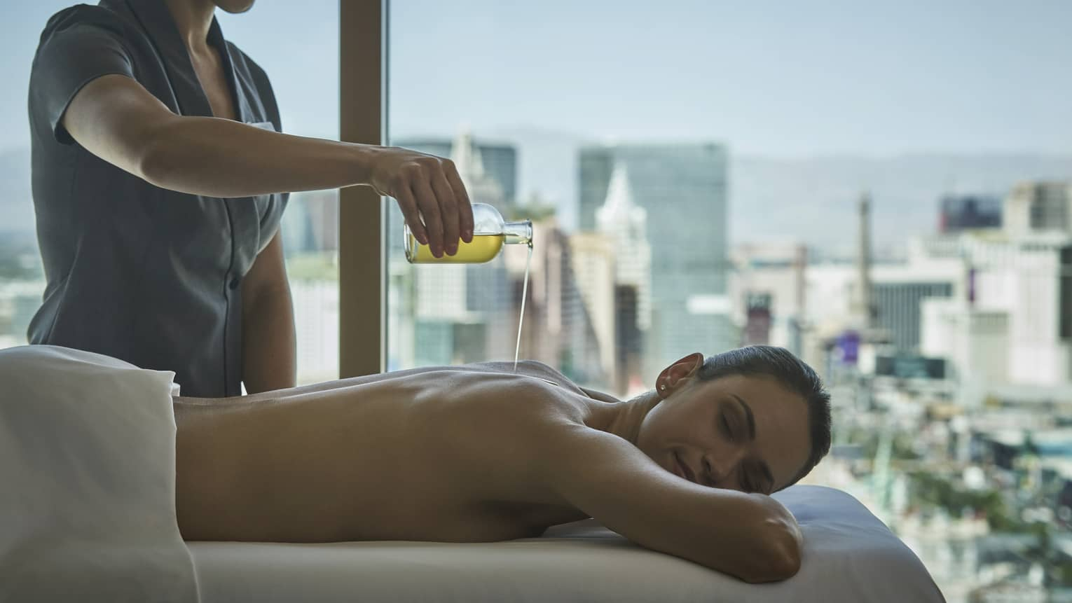 A woman with eyes closed lies on massage table and receives a treatment in a room with a view of the city skyline