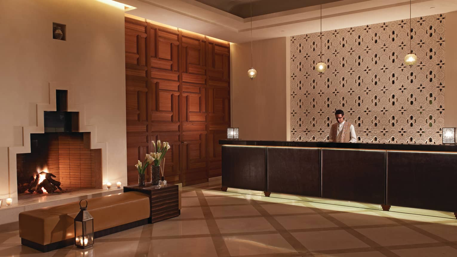 Four Seasons Resort Marrakech modern white hotel lobby with fireplace, bench, lanterns by reception desk