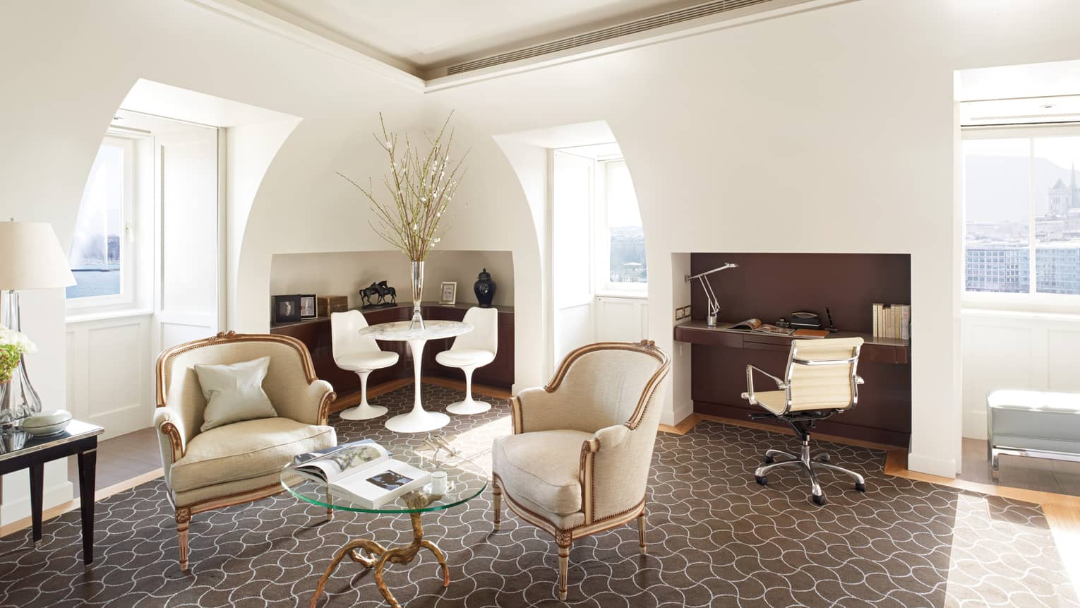 Bright Executive Loft Suite with sloped white ceilings, recessed windows, cream armchairs, modern white cafe table