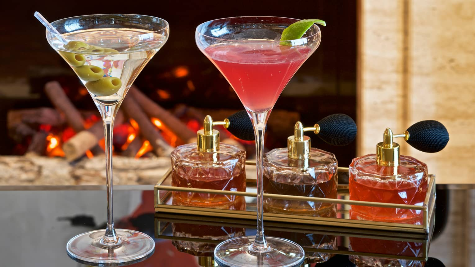 Two martinis on counter, one with olive spear and the other with pink liquid, lime garnish