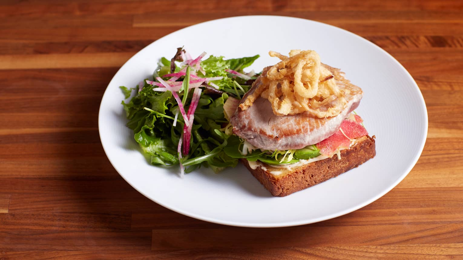 White plate with open-faced Ahi-tuna sandwich with fried crispy shallots, green garden salad on side