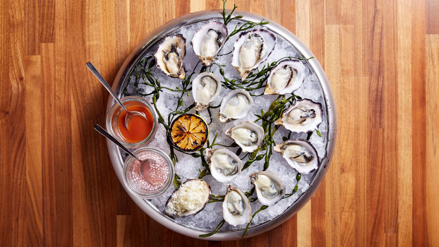 Aerial view of round silver platter with half shells and fresh oysters on ice, roasted lemon half and sauce bowls