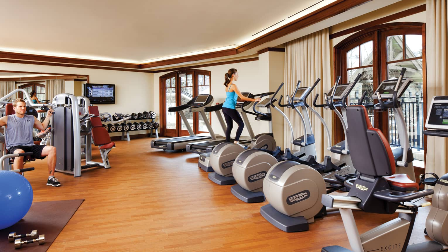 Woman on elliptical in row of cardio machines, man bench presses weights behind