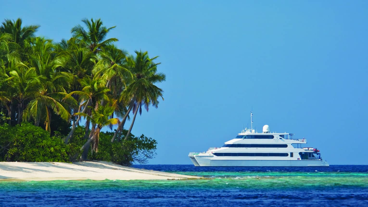 Four Seasons Explorer large white luxury catamaran near lagoon by sand beach, palm trees