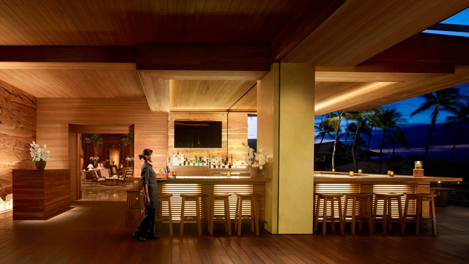 Server walks by wood NOBU Lanai restaurant bar with lights on indoor outdoor patio at night