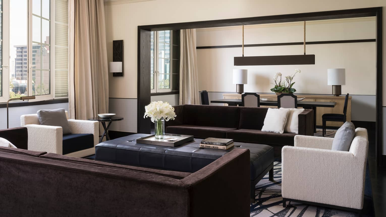 Presidential Suite bright living room with long sofas, white armchairs, tall sunny window, dining room