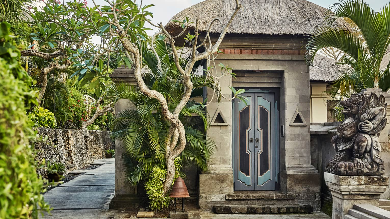 Stone wall, steps by tall rustic blue door under thatched roof, twisted tropical trees