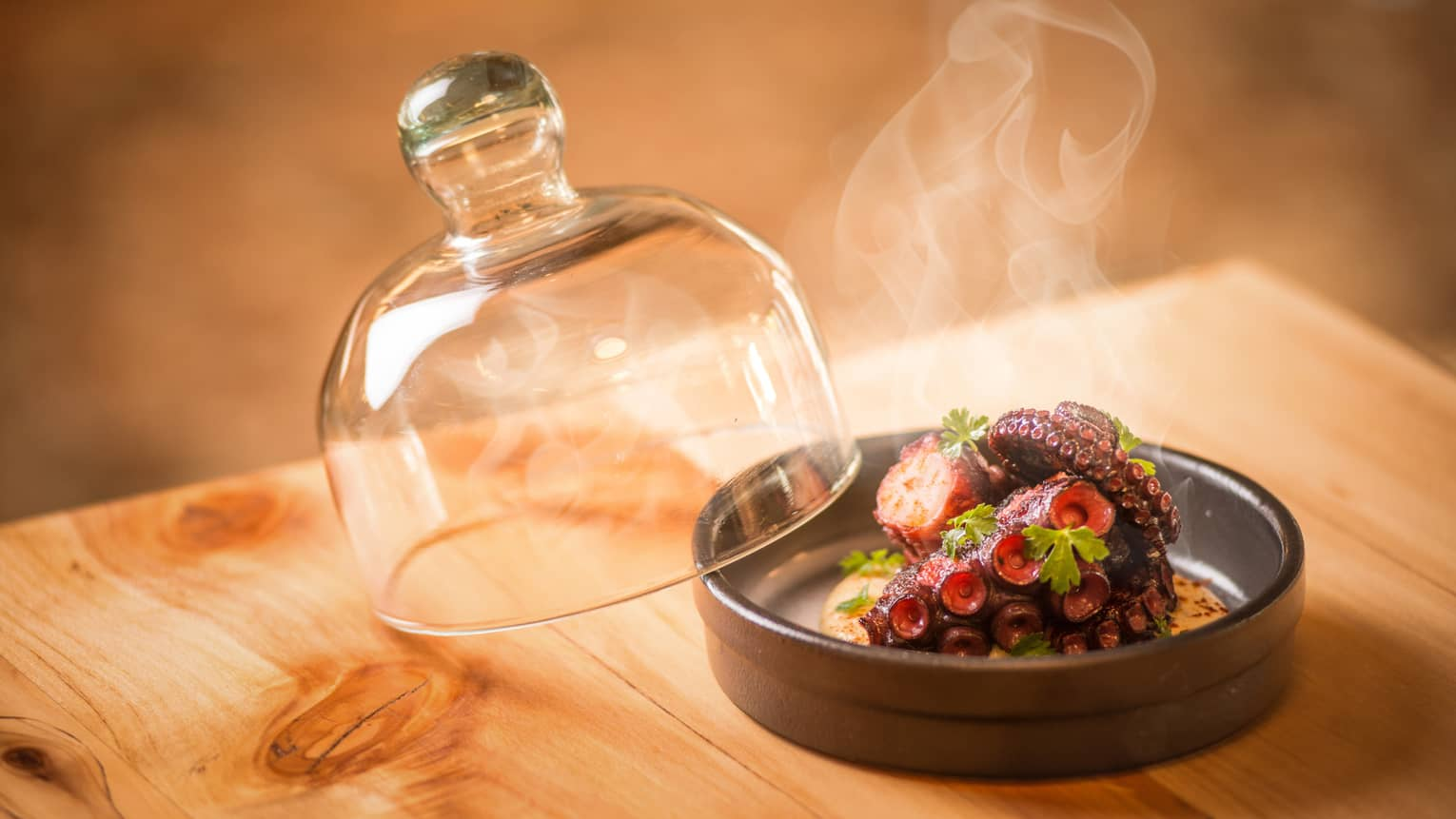 Steam rises from Grilled Octopus in round black dish with glass lid