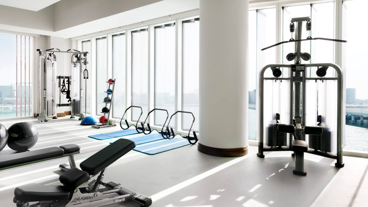 Fitness centre with sunny corner windows, weightlifting and cardio machines, three yoga mats
