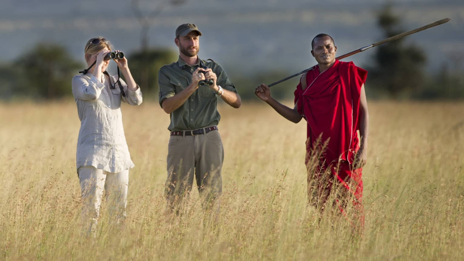 Couple takes photos on walking safari through tall grass with guides