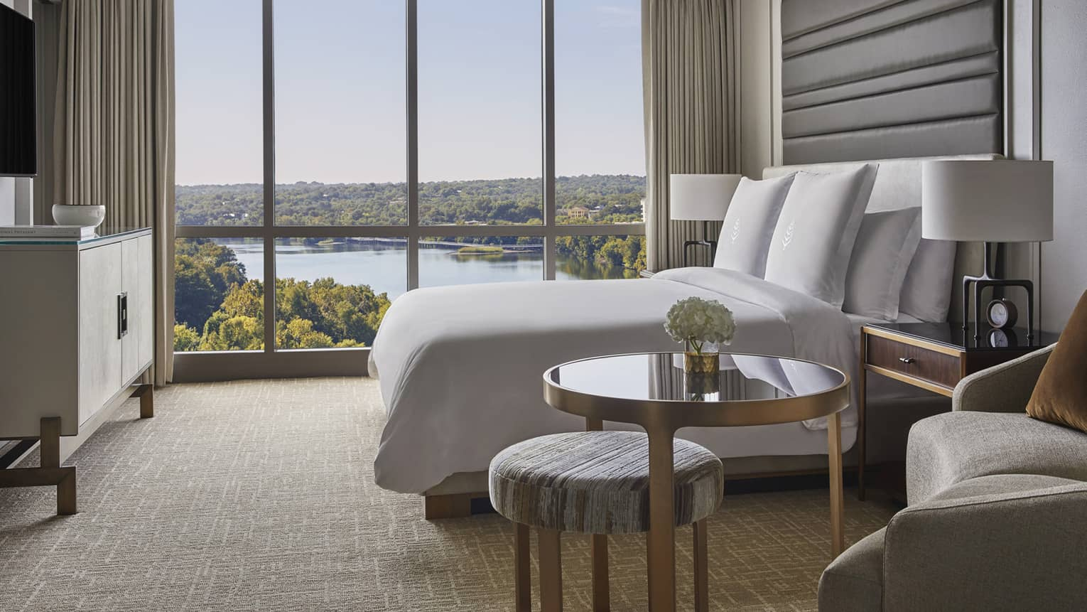 Side view of small brass and glass table, hotel bed by floor to ceiling window and lake views