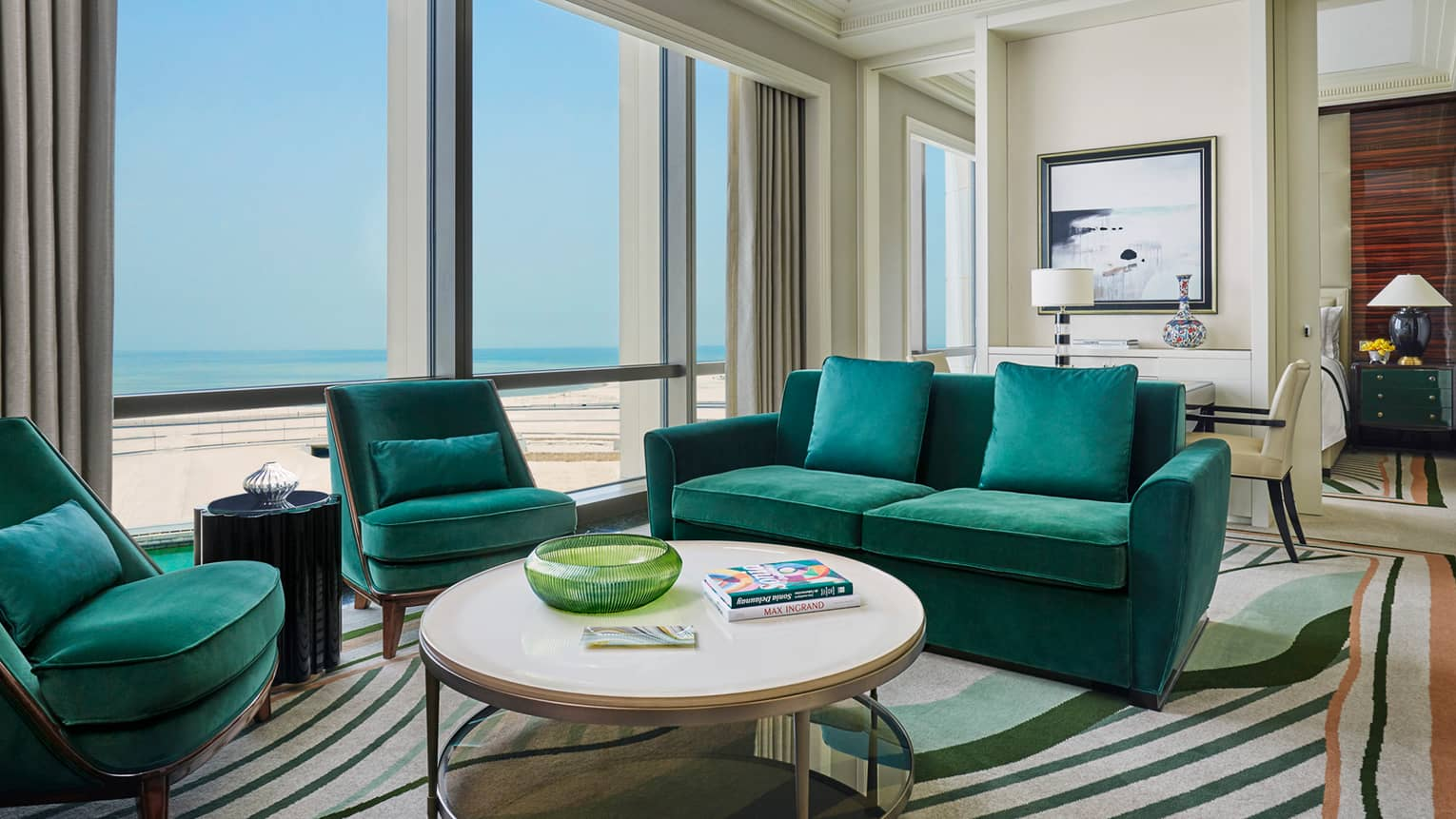 Four Seasons Executive Suite with emerald green velvet sofas, armchairs, round coffee table with books, sunny windows