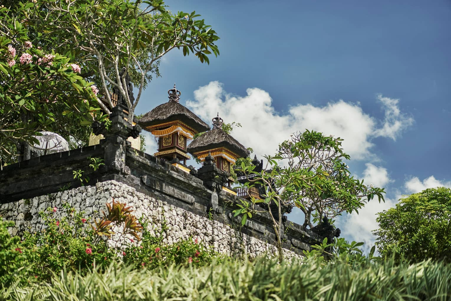 Exterior view of resort temple with stone wall, posts and carvings, tropical trees