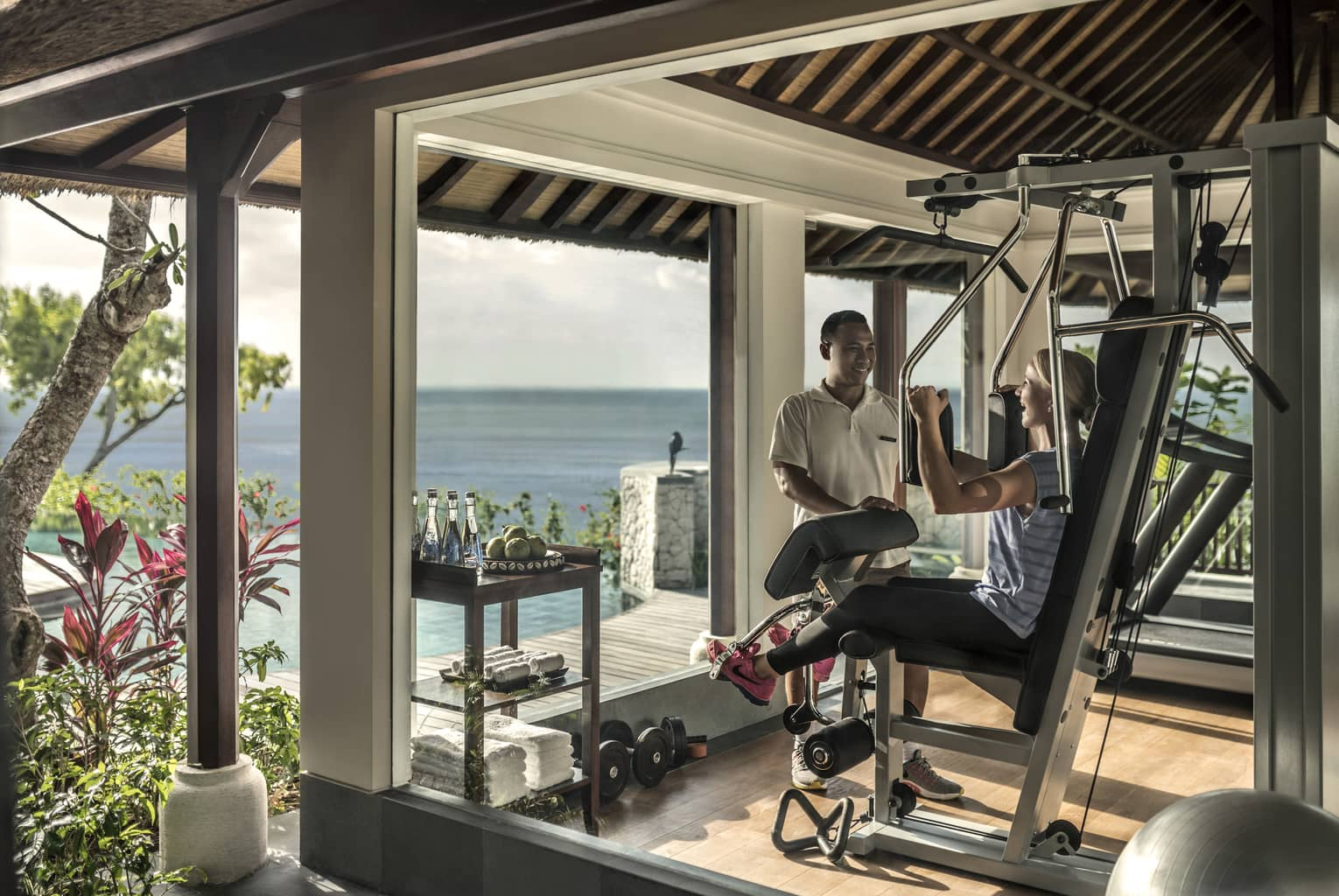Imperial Villa private gym, trainer assists woman on weights machine by window with ocean view