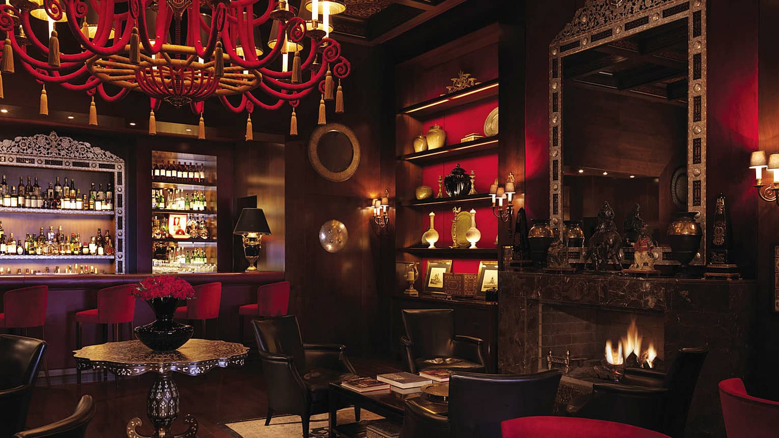 Bar interior with dark wood, red chandelier, shelf and velvet bar stools, arabesque ceiling, fireplace