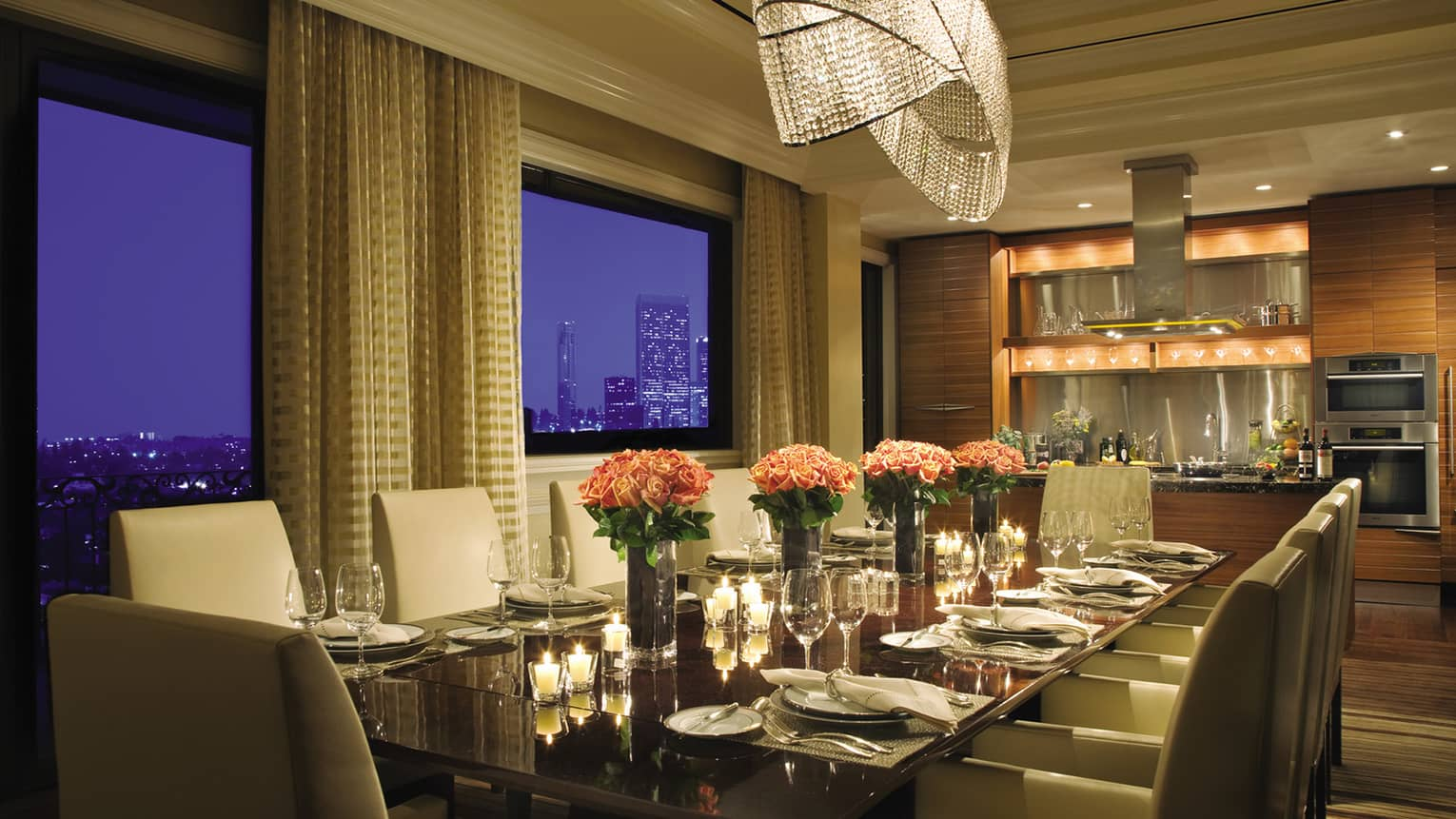 Penthouse Suite private, candlelit dining table with pink roses by windows, kitchenette at night