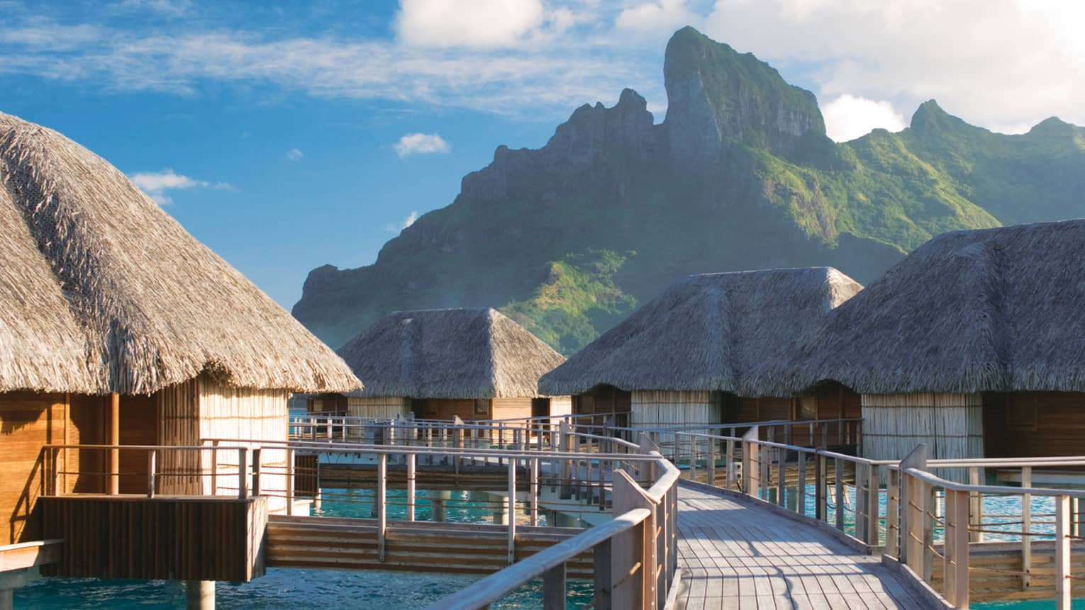 Curved deck connecting overwater bungalows with thatched roofs above lagoon