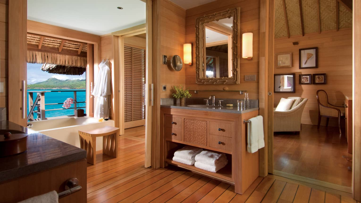 Large bathroom with wood decor, sink and vanity, full-length mirror and bathtub looking out at ocean
