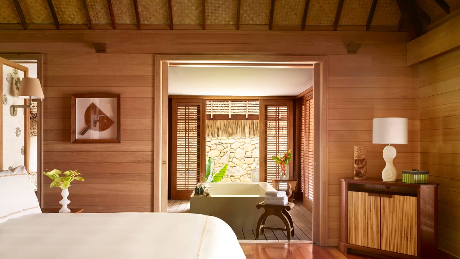 Fenua beachfront villa bedroom with white bed, wood decor, looking into room with square spa tub, patio door