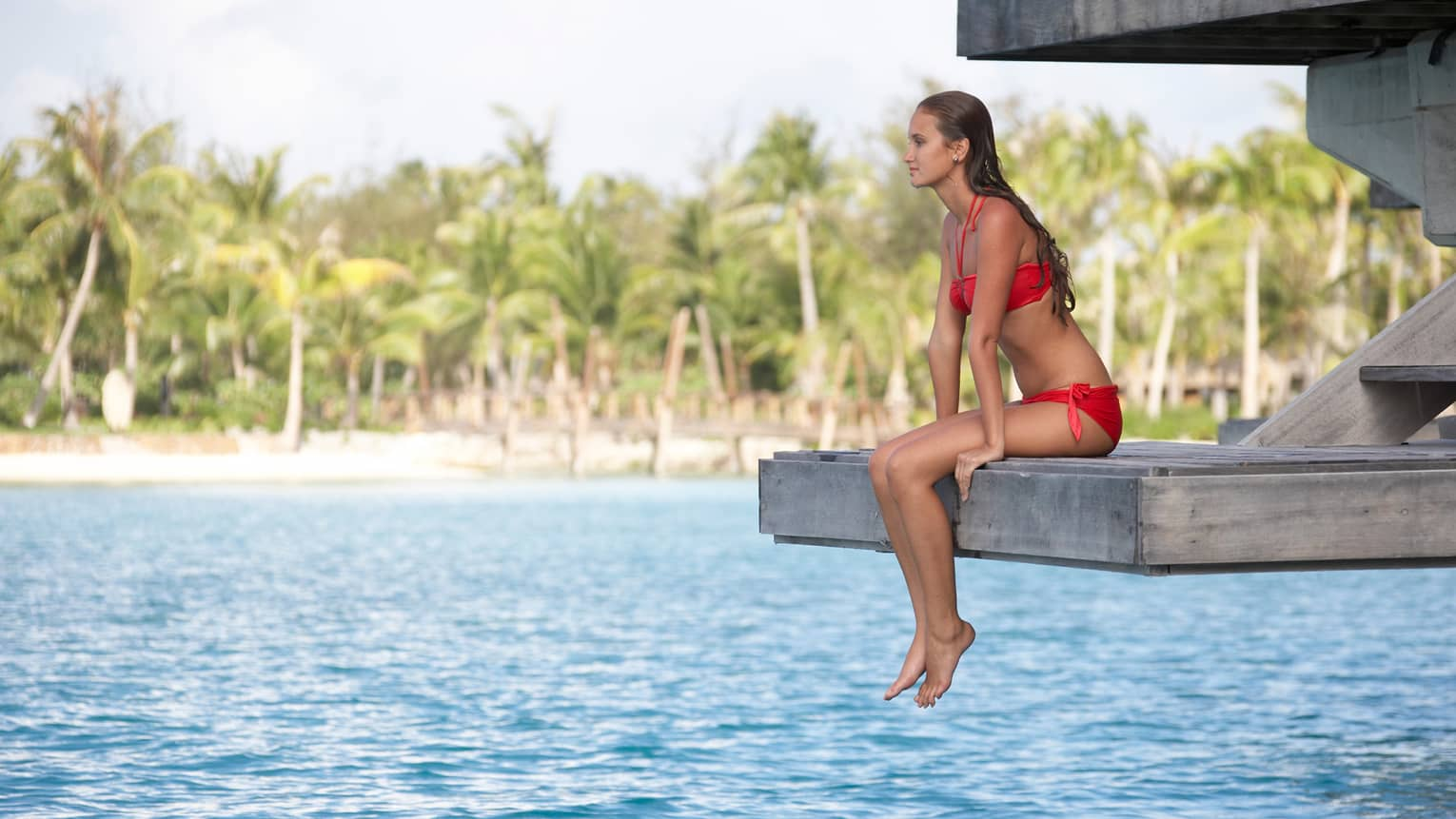 Woman in red bikini sits on end of overwater bungalow deck, ocean below