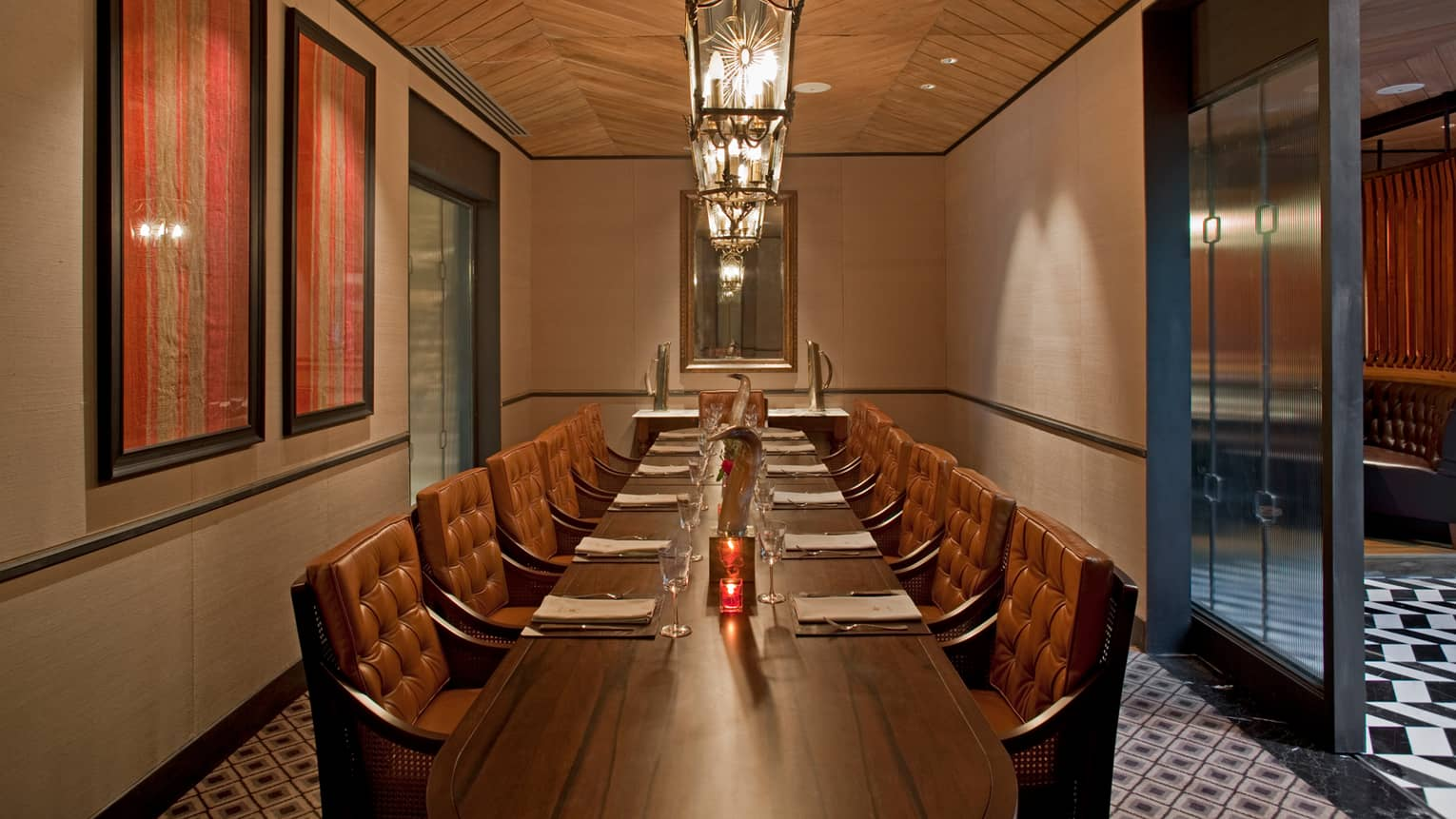 Long wood private dining table with padded brown leather chairs under row of lights, framed art on wall