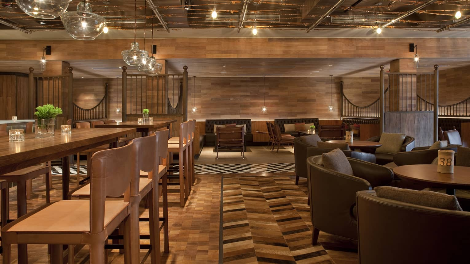Pony Line lounge with rich brown wood flooring and walls over tables with stools, leather chairs, glass chandeliers