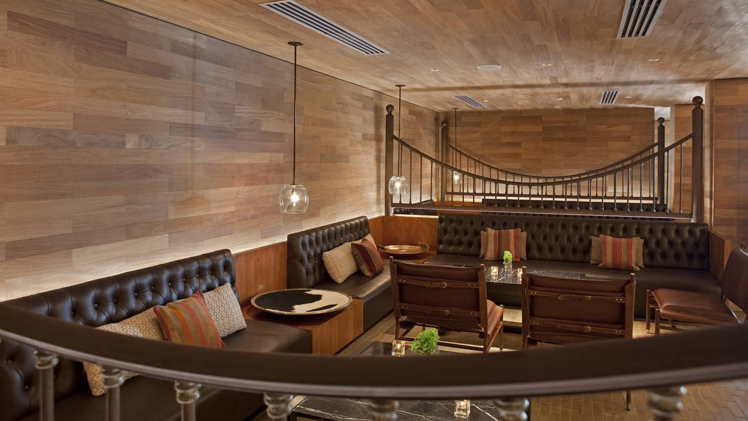 Pony Line view over curved railing to leather banquettes, lounge seating area against wood wall