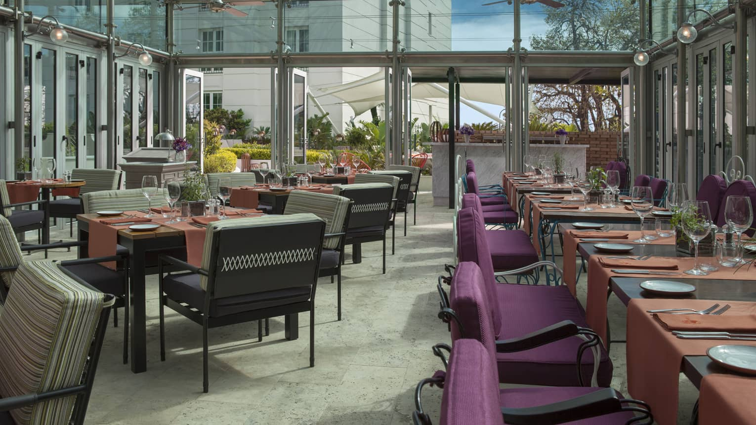 Nuestro Secreto outdoor dining room in glass patio with purple chairs, orange linens on table