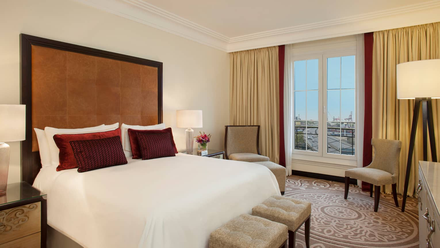 City-View One Bedroom Suite bed with tall padded leather headboard, small red accent pillows, two chairs by window