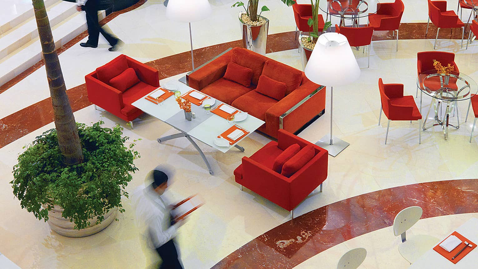 Aerial view of server walking quickly through Beymen Cafe, past red sofas and chairs and indoor tree