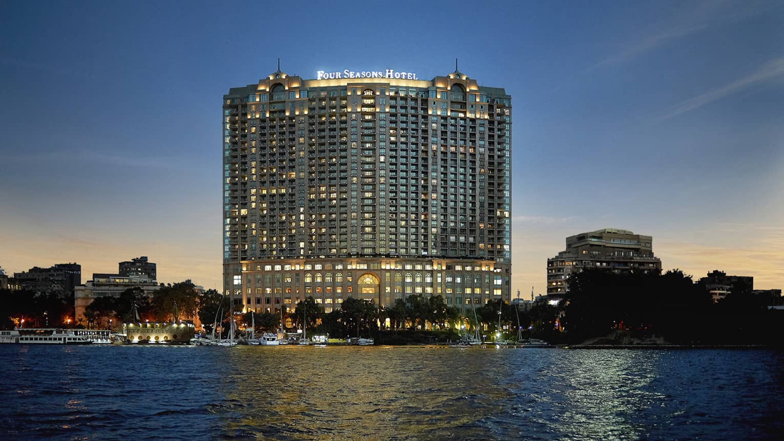 Hotel exterior illuminated at dusk, along the Nile River