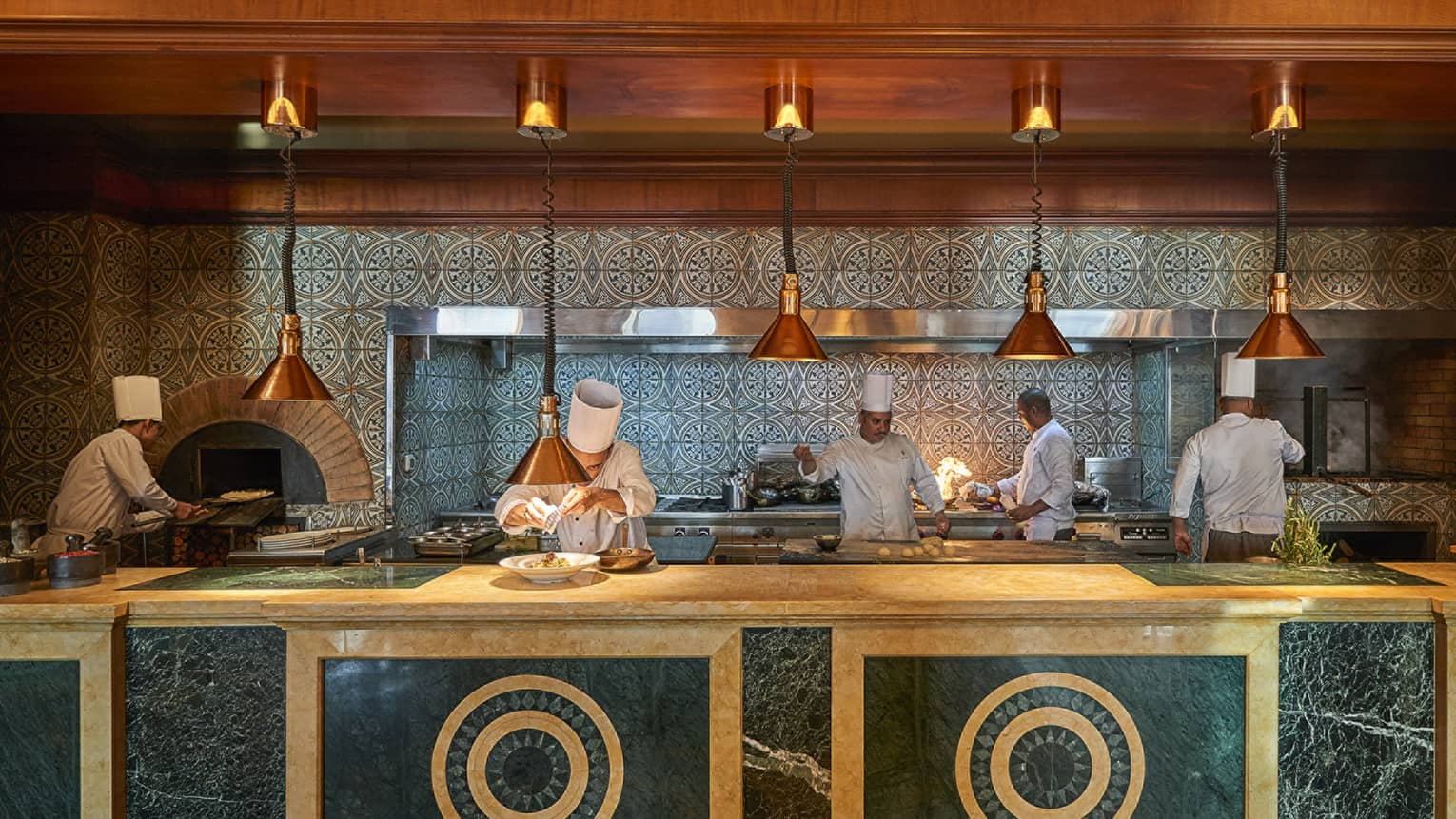 Bella chefs in white coats and hats prepare meals on large cream-and-brown marble counter under brass lamps