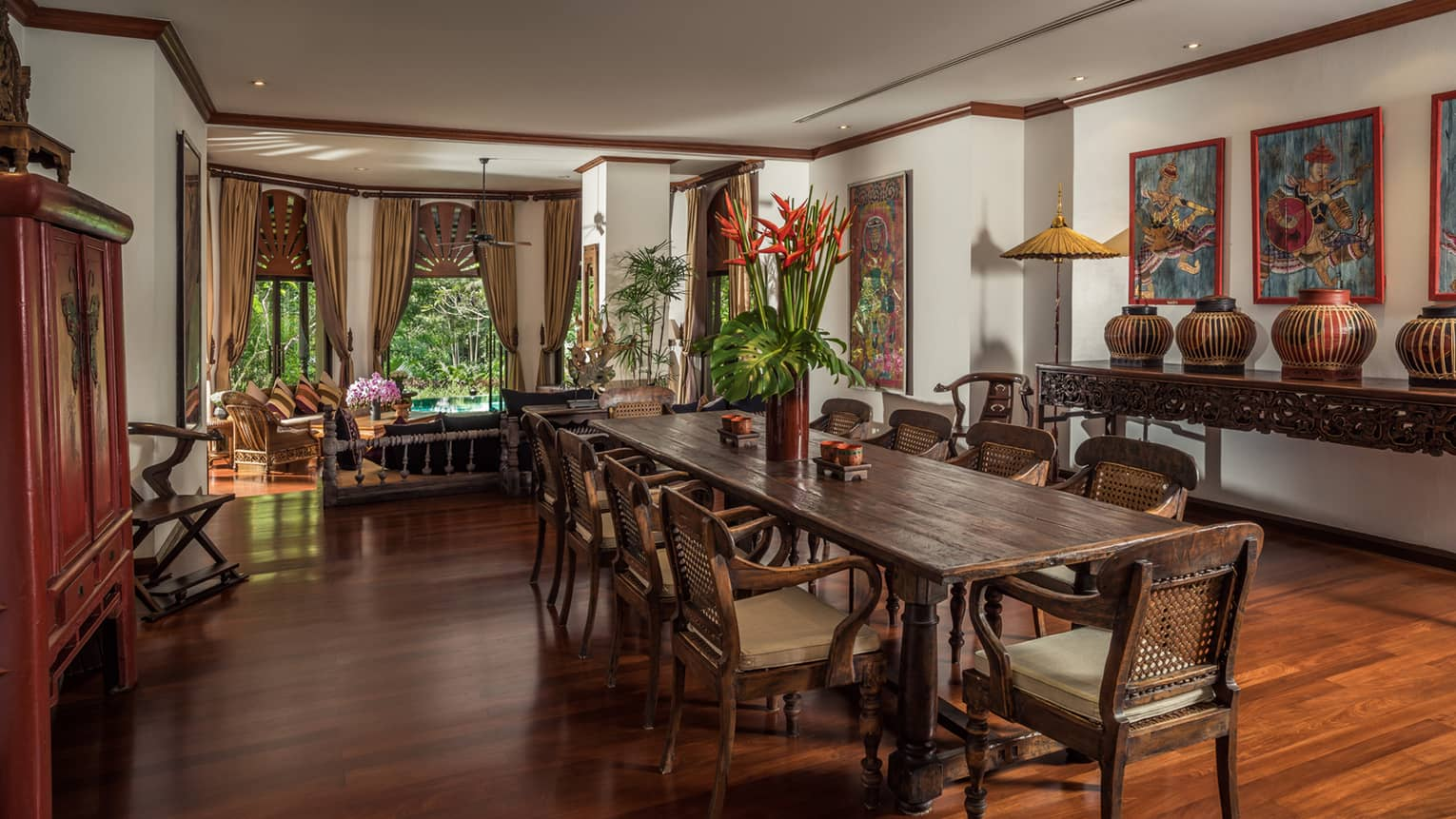 Long wood dining table with vase with tall tropical flowers in bright room