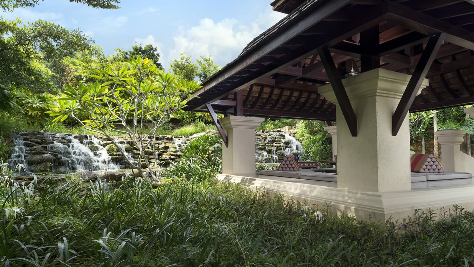 Large pavilion by stone waterfall, tropical gardens