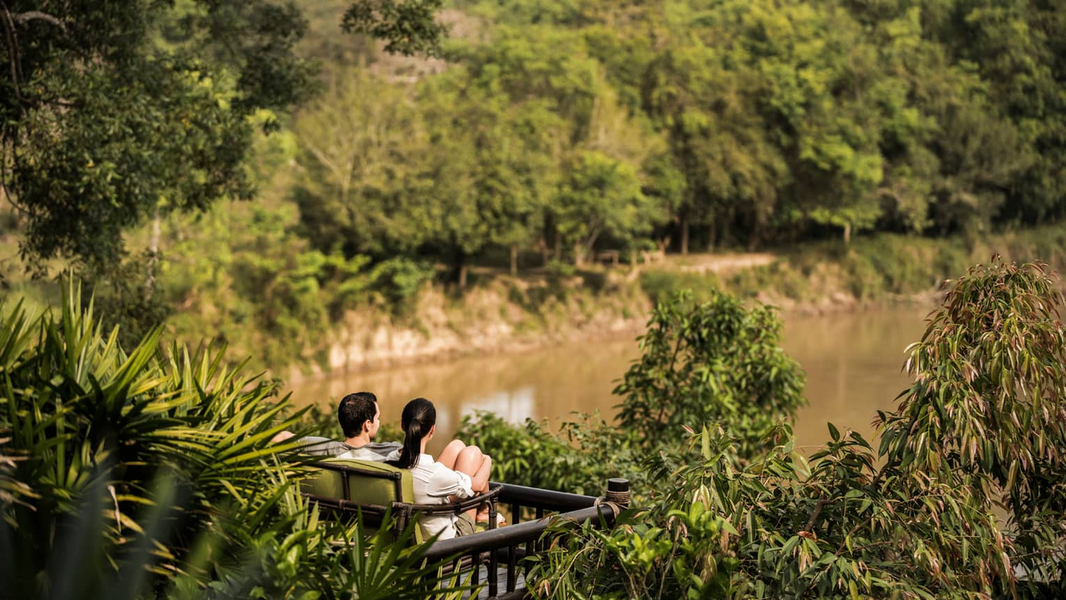 Couple sits on wood bench surrounded by tropical plants, overlooking river