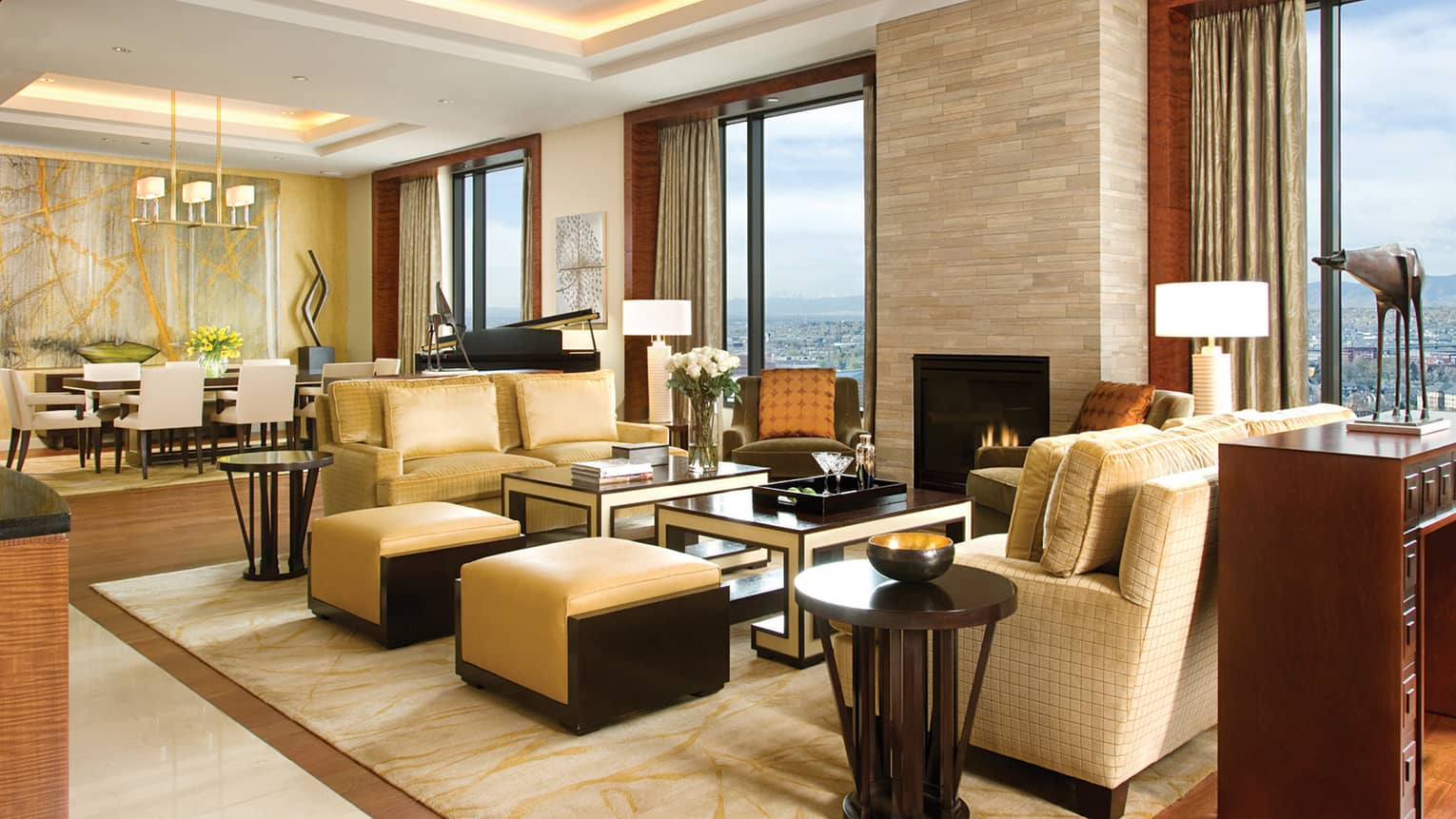 Presidential Suite large plush beige sofas, ottomans, table, fireplace, high ceilings, modern art