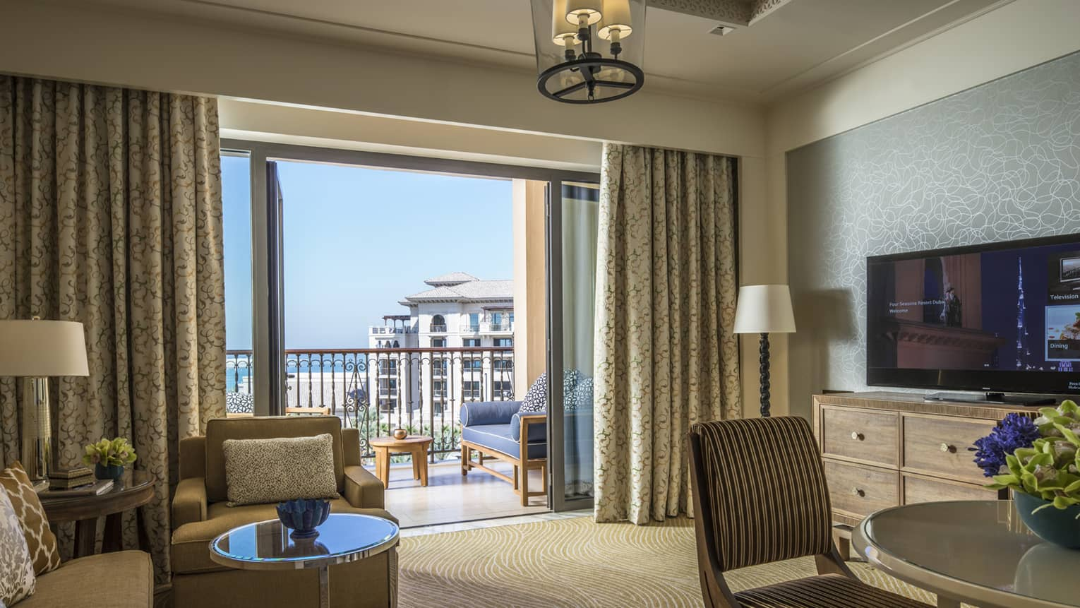 Four Seasons Sea-View Suite with large living and dining space, flat-screen TV, balcony