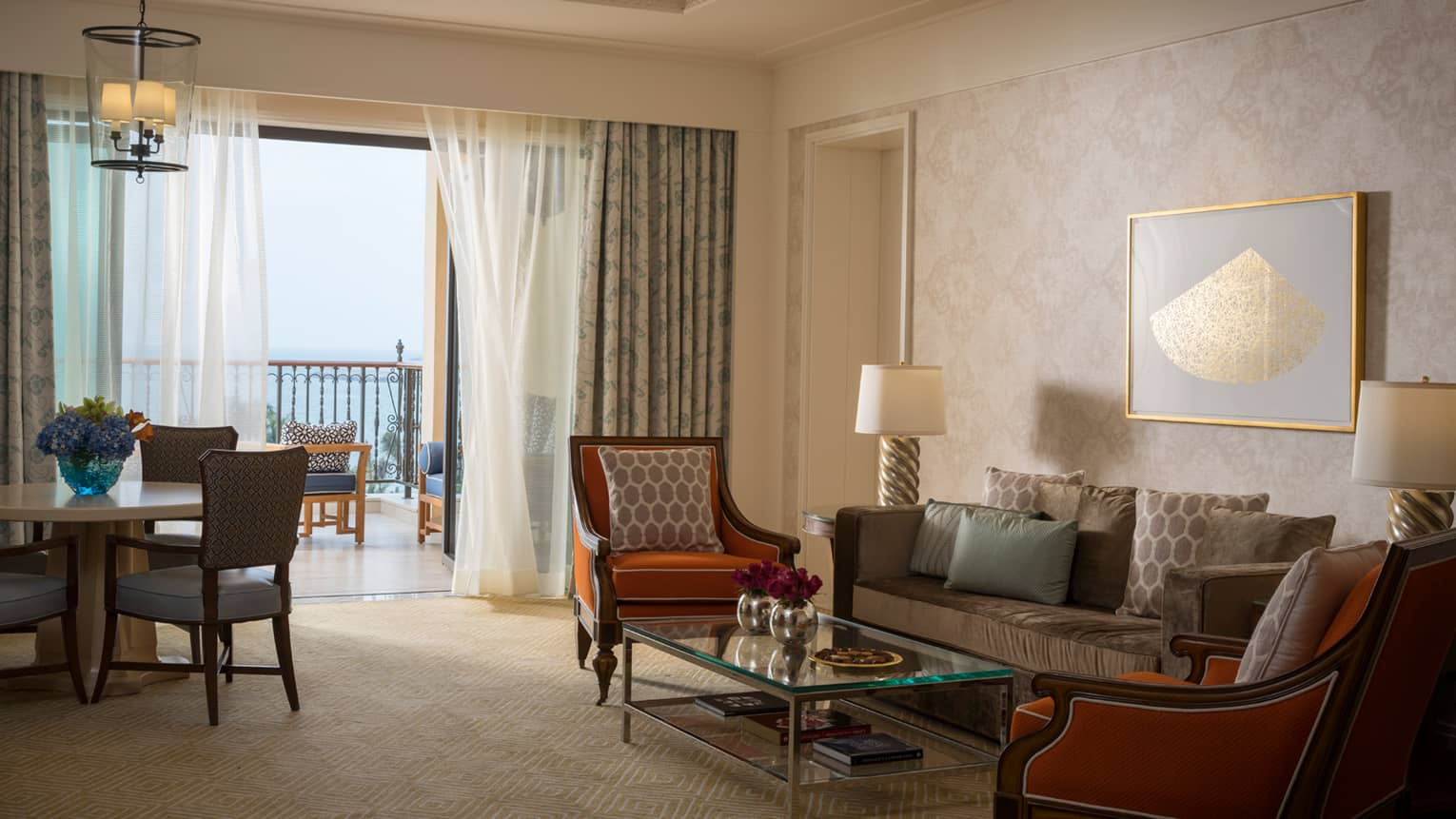 Jumeirah Sea-View Suite with large living space, orange and gold accents, white curtains