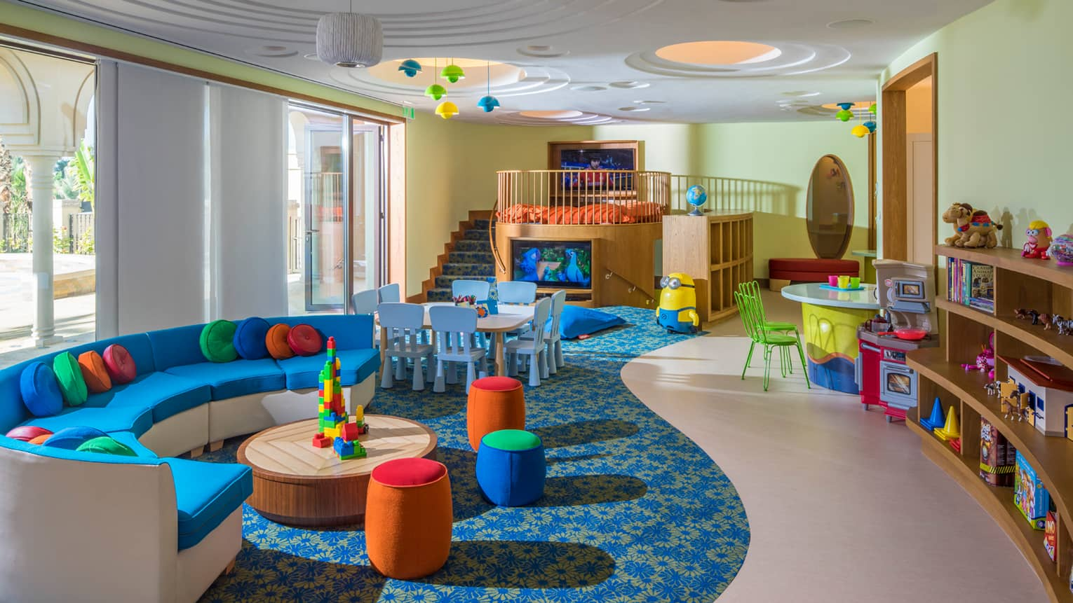 Complimentary kids centre room with curved, bright sofa and cushions, toys and TV loft