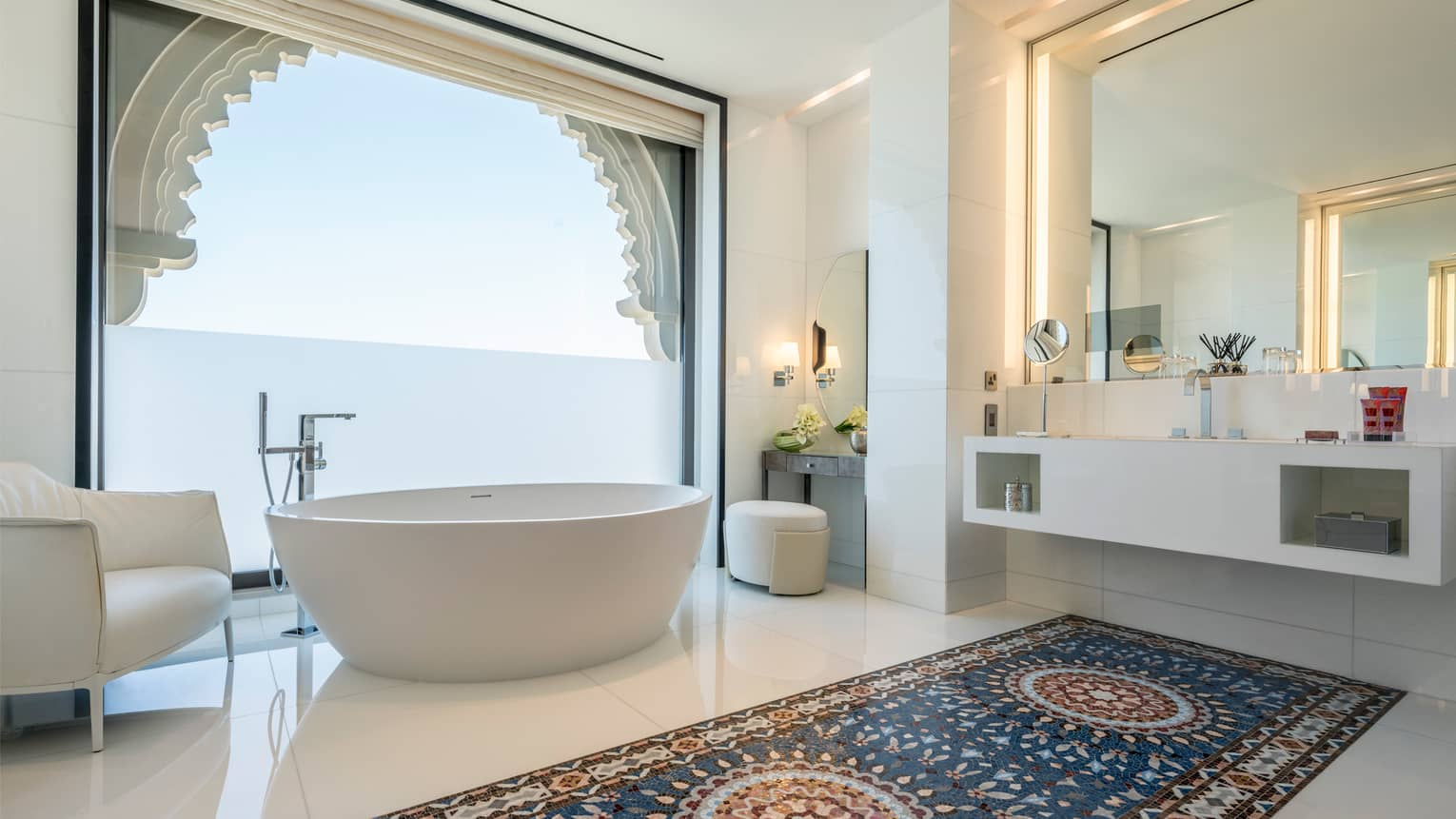 Bathroom with white spa tub and armchair in front of tall window and vanity, white floors with Arabic-style tiles