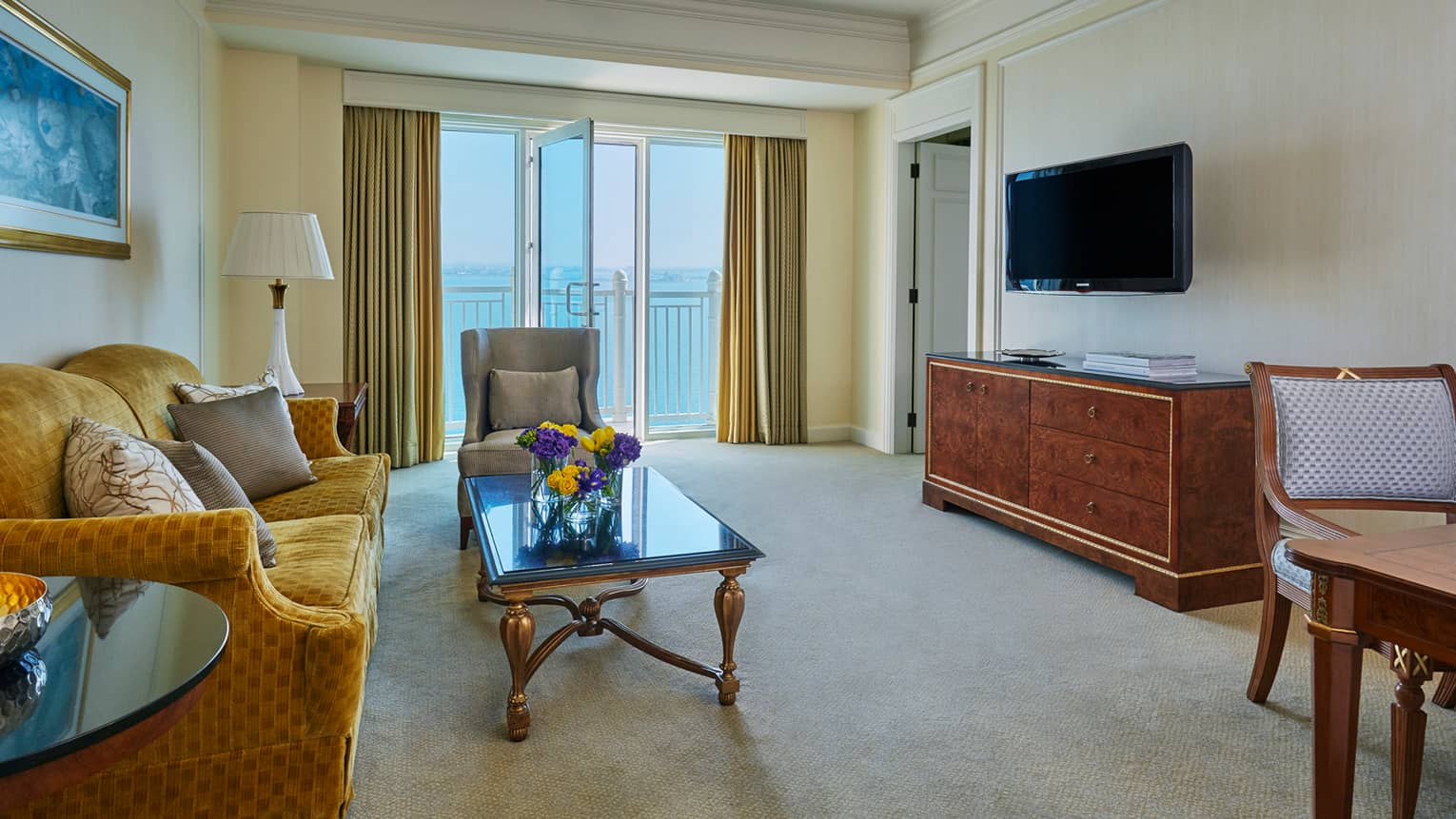 Deluxe Four Seasons Executive Suite living room with gold plush sofa, coffee table, wood dresser