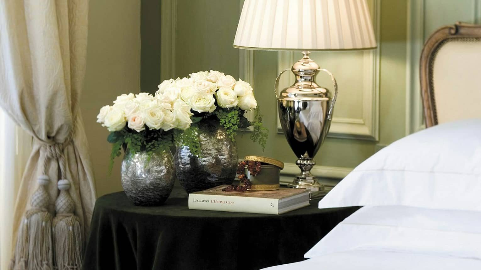 Superior Room silver lamp, vases with white roses, book on nightstand